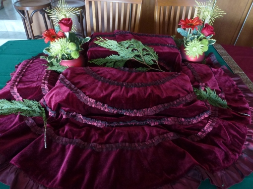 Buffet table with tablecloth and tree skirt over risers.