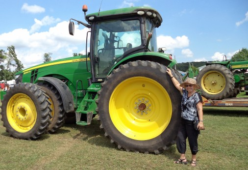 DSC00477 Lois demonstrates the size of the new farm tractors.