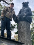 7 Standing atop his ATV, Mike mounts the bearstatue