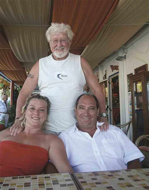 Gunter stands behind Angela and her husband, owners of the Stella del Sud Marina. The Long Way Back, page 410.